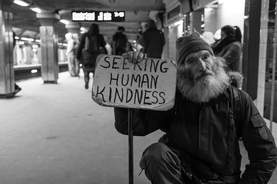 """Bearded old man sitting in subway station holds sign that says, """"Seeking Human Kindness."""""""